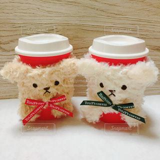 コーヒー カップの横に座っている赤と白のテディベアの写真・画像素材[935936]