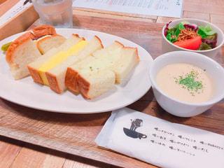 木製のテーブルの上に食べ物のプレートの写真・画像素材[1702849]