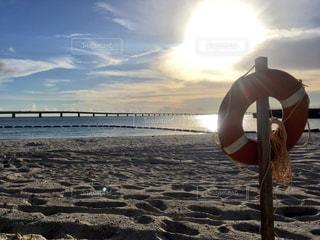 海の横にある砂浜に立っている人の写真・画像素材[772588]