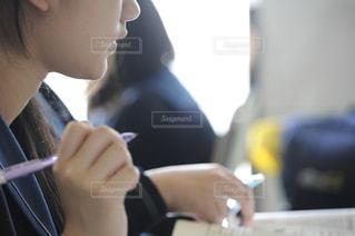 ペンを持つ授業中の女子高生の写真・画像素材[771200]