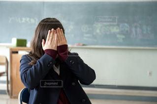 教室で顔を隠す女子高生の写真・画像素材[907368]