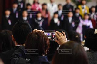 小学校の卒業式で写真を撮る保護者の後ろ姿の写真・画像素材[1092254]