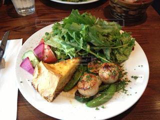 木製のテーブルがサンドイッチと皿にサラダをトッピングの写真・画像素材[854819]