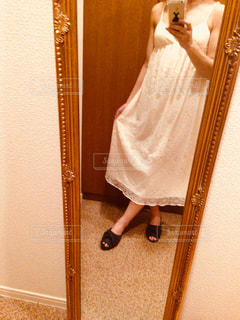 カメラにポーズ鏡の前に立っている人の写真・画像素材[1201466]