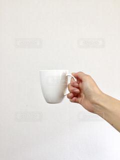 ミルクのガラスを持っている手の写真・画像素材[1209756]