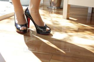 いくつかの靴で、テーブルに座っている女性の写真・画像素材[1209821]