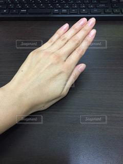 木製の机の上でパソコンを打つ前の女性の手の写真・画像素材[1681517]