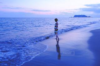 水の体の横に立っている人の写真・画像素材[706181]