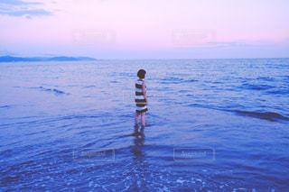 水の体の横に立っている人の写真・画像素材[706182]