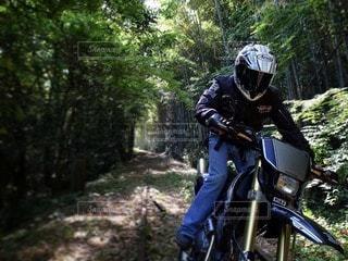未舗装の林道をバイクに乗る男の写真・画像素材[3099973]