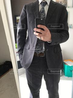 携帯電話で話しているスーツとネクタイを着た男の写真・画像素材[2898989]