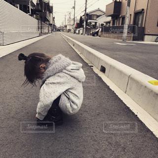 歩道の上に座っている女性の写真・画像素材[706604]