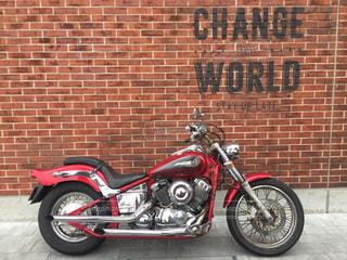 れんが造りの建物の前に停まっている赤いバイク - No.706477