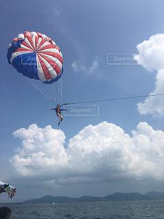 パラシュートは曇りの日に空気を通って飛んでいます。の写真・画像素材[706590]