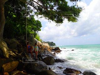 水の体の横にある岩の上の人々 のグループの写真・画像素材[707144]