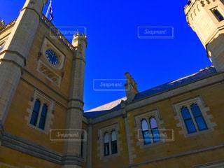 建物の側に時計と大きな背の高い塔の写真・画像素材[707954]