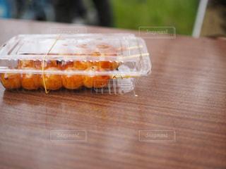 近くの木製のテーブルの上に食べ物をの写真・画像素材[716448]