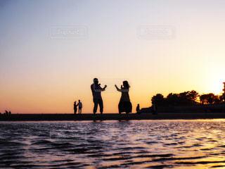 水の体の横に立っている人の写真・画像素材[1180475]