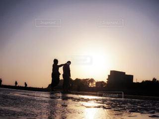 バック グラウンドで夕日を持つ男の写真・画像素材[1180479]