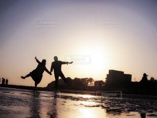 バック グラウンドで夕日を持つ男の写真・画像素材[1180480]