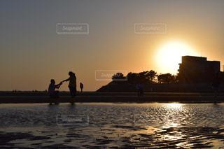 水の体の横に立っている人の写真・画像素材[1180495]