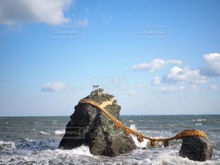 水の体の横にある岩の上に座っている男の写真・画像素材[1783818]