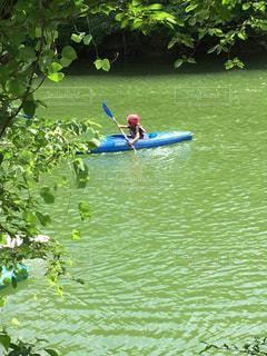 水のボートの背に乗る男の写真・画像素材[708985]