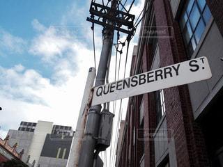 近くの建物の側面を離れて掛かる道路標識 - No.709064