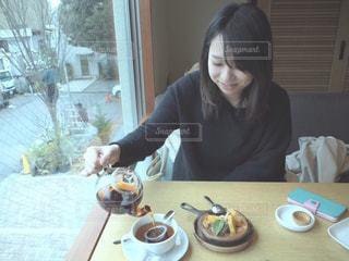 テーブルに座っている女性の写真・画像素材[735601]