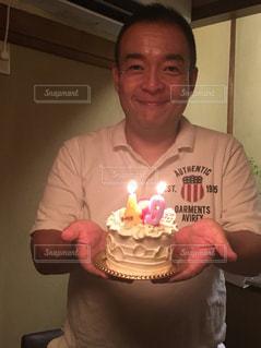 キャンドルで誕生日ケーキを持っている人の写真・画像素材[1477442]