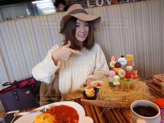 食品のプレートをテーブルに座っている女性の写真・画像素材[964580]