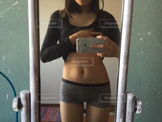 カメラにポーズ鏡の前に立っている人の写真・画像素材[790383]
