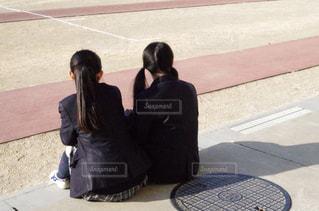 歩道の上に座っている人の写真・画像素材[1056606]