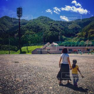 山の前に立っている人のカップル - No.710573