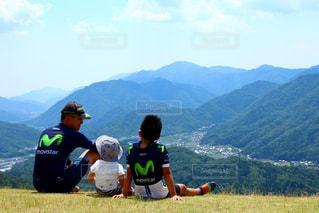 山の上に座っている男の写真・画像素材[710623]