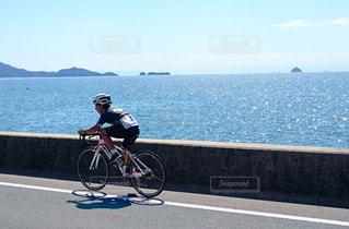 水の体の横に自転車に乗る男 - No.712681