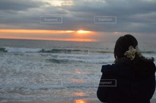 ビーチの日没の前に立っている女性の写真・画像素材[710650]