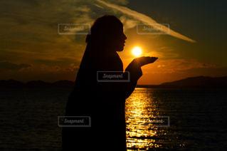 水の体の上に日没の前に立っての写真・画像素材[712724]