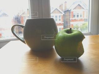 ウィンドウの前面に青リンゴとデスクの写真・画像素材[716743]