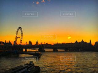 バック グラウンドで市と水体に沈む夕日の写真・画像素材[718689]