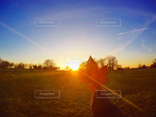 バック グラウンドで夕日を持つ男の写真・画像素材[720852]