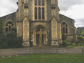 大規模な石造りの教会の前の芝生と建物の写真・画像素材[743008]