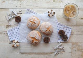 木製のテーブルの上に座って半分食べるドーナツの写真・画像素材[1376682]