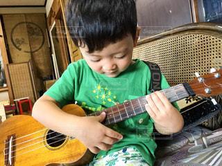 ギターの隣に座っている少年の写真・画像素材[711436]