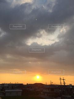 雲に覆いかぶされる夕日の写真・画像素材[712655]