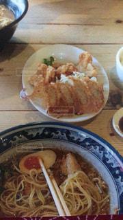 テーブルの上の皿の上に食べ物のボウルの写真・画像素材[712579]