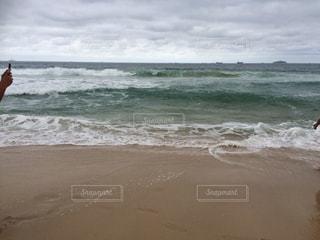 海の横にあるビーチの上を歩く人 - No.715127