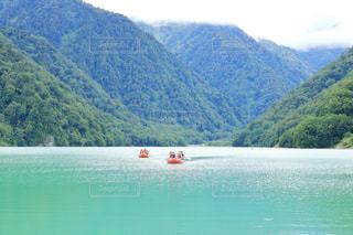 背景の山と水上のボート(岐阜県 白水湖)の写真・画像素材[885617]