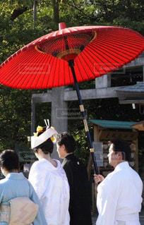 赤い傘の周りに立って人々 のグループの写真・画像素材[725848]