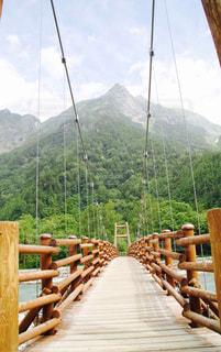 山の前に座っている木製のベンチの写真・画像素材[732324]